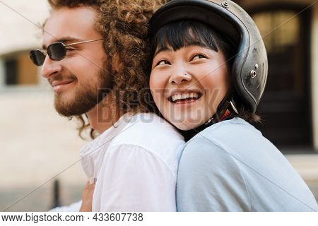Happy young multiethnic couple on scooter enjoying ride on a street close up
