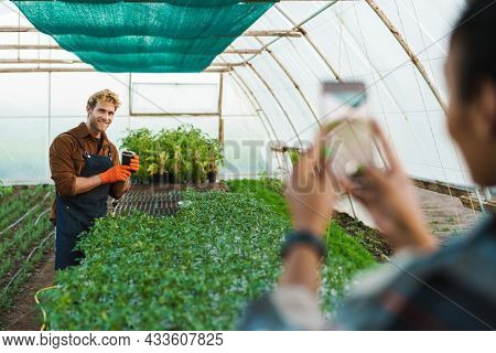 Happy middle aged multiethnic couple of farmers working in a greenhouse together woman taking a picture of a smiling men holding plant