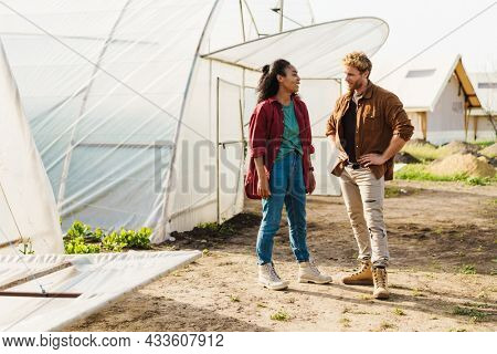 Happy middle aged multiethnic couple of farmers working in a greenhouse together talking discussing work