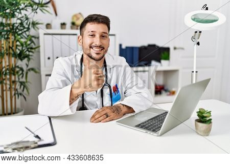 Young doctor working at the clinic using computer laptop doing happy thumbs up gesture with hand. approving expression looking at the camera showing success.