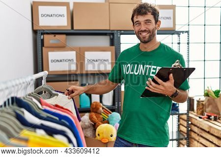 Young hispanic volunteer man smiling happy working at charity center.