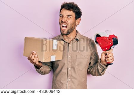 Handsome man with beard holding packing tape holding cardboard angry and mad screaming frustrated and furious, shouting with anger. rage and aggressive concept.