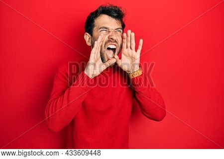 Handsome man with beard wearing casual red sweater shouting angry out loud with hands over mouth