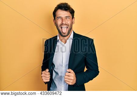Handsome man with beard wearing business suit holding jacket sticking tongue out happy with funny expression.