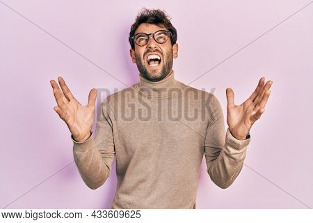 Handsome man with beard wearing turtleneck sweater and glasses crazy and mad shouting and yelling with aggressive expression and arms raised. frustration concept.