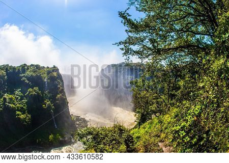 Victoria National Park. Giant cloud of water fog over Victoria Falls. The waterfall on the Zambezi River. Journey after the wet season. Concept of extreme and photo tourism