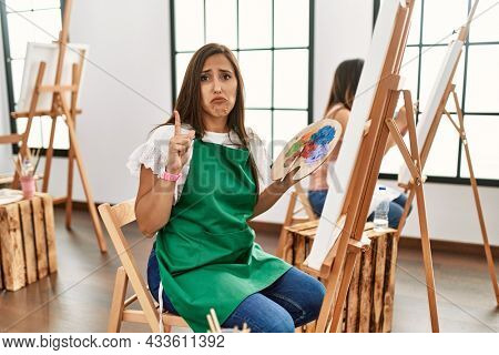 Young hispanic artist women painting on canvas at art studio pointing up looking sad and upset, indicating direction with fingers, unhappy and depressed.