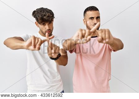 Young gay couple standing over isolated background rejection expression crossing fingers doing negative sign