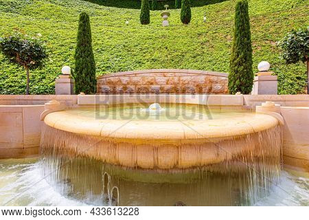 Marble fountain on a steep mountainside. Gorgeous flower beds, cypress and green lawns attract pilgrims and tourists. Mount Carmel in Haifa. Israel. Clear sunny day by the sea.