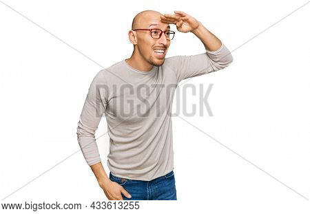 Bald man with beard wearing casual clothes and glasses very happy and smiling looking far away with hand over head. searching concept.