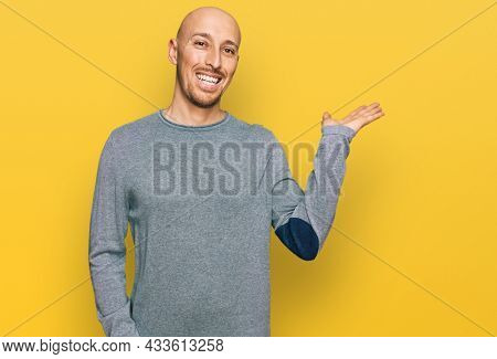 Bald man with beard wearing casual clothes smiling cheerful presenting and pointing with palm of hand looking at the camera.