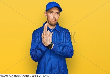 Bald man with beard wearing builder jumpsuit uniform holding symbolic gun with hand gesture, playing killing shooting weapons, angry face