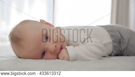 Portrait of a newborn baby looking. One-month-old baby is lying on his tummy in light clothes. White calm little boy looking away. Close-up of a cute boy's face.