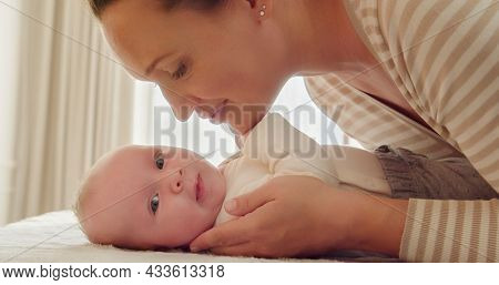 Young Mother looks in her newborn baby. Closeup portrait of a loving mother's kiss.  Happy mom looking beautiful  infant son. Mum loves of her infant child. Parenthood concept. Happy mom, happy kid.