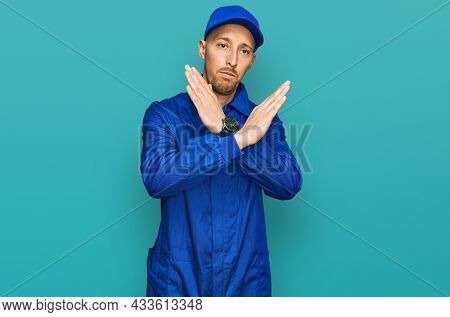 Bald man with beard wearing builder jumpsuit uniform rejection expression crossing arms doing negative sign, angry face