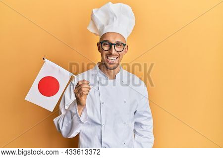 Bald man with beard wearing professional cook uniform holding japan flag looking positive and happy standing and smiling with a confident smile showing teeth