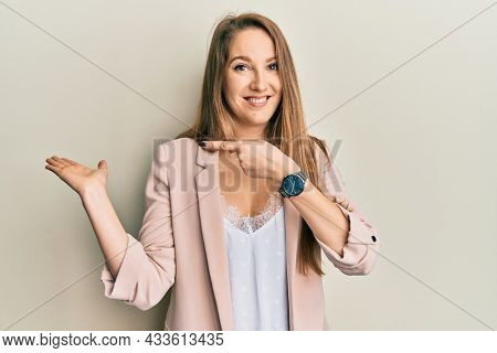 Young blonde woman wearing business jacket and glasses amazed and smiling to the camera while presenting with hand and pointing with finger.