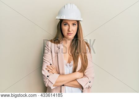 Young blonde woman wearing architect hardhat relaxed with serious expression on face. simple and natural looking at the camera.