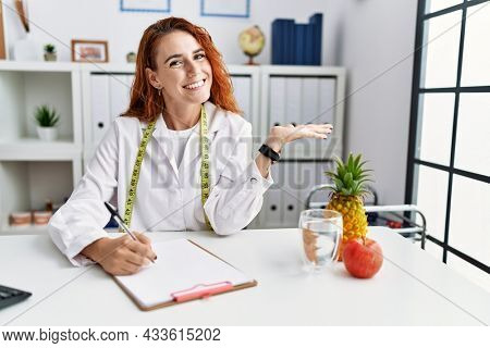 Young redhead woman nutritionist doctor at the clinic pointing aside with hands open palms showing copy space, presenting advertisement smiling excited happy