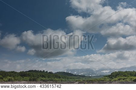Volcanoes With Snow-covered Slopes Rise Against The Blue Sky. The Peaks Are Hidden In Fluffy Clouds.