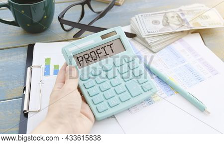 Office Desktop With Calculator Displaying The Word Profit. Profit Calculation, Profitability, Busine