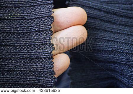 Fingers On A Hand In A Black Woolen Sweater Sleeve