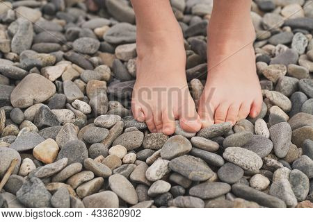 Prevention Of Flat Feet In Children. The Child Walks On The Stones With His Bare Feet. Treatment Of