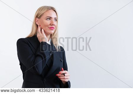 Attractive Blonde Woman In Business Suit Stands On Background Of A White Wall. Successful Female Man