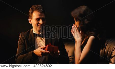Happy Young Man In Suit With Bow Tie Giving Present To Stunned Woman Isolated On Black
