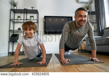Smiling Sporty Toned Father And Son Exercise Workout Together At Home. Happy Active Fit Caucasian Da