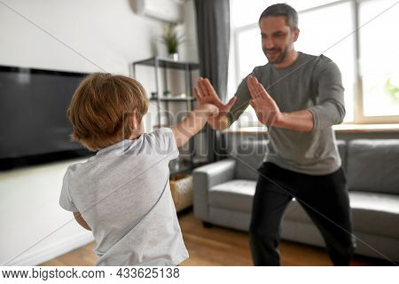 Close Up Focus Of Sporty Teen Boy Child Have Training Workout With Dad At Home. Active Teenage Cauca