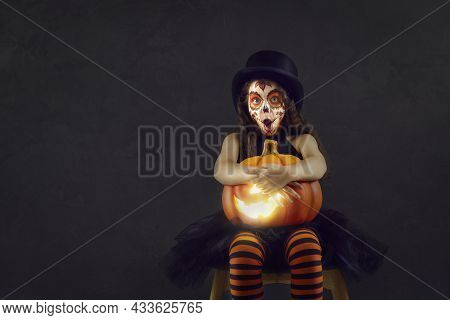 Shocked Little Girl In Halloween Clothes Sitting With Jack-o-lantern On Black Background.