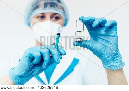 A Female Doctor In A Medical Face Mask And Gloves Dials The Vaccine Into A Syringe From An Ampoule.
