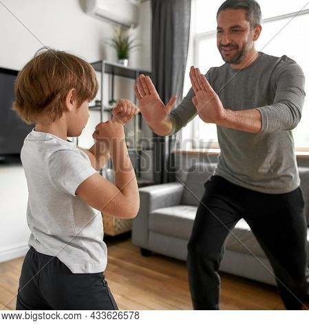 Narrow Vertical Shot Of Active Teen Boy Child Practice Beat Knock Train With Father At Home. Sporty