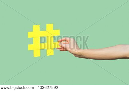 Social Media Concept, Closeup Portrait Of Hand Holding Large Big Yellow Hash Tag Sign. Indoor, Isola