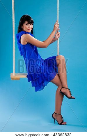 Girl In The Blue Dress Sitting On Swings