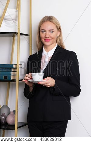 Vertical Portrait Of Attractive Blonde Business Woman In Business Suit. Woman Holding A White Cup Wi