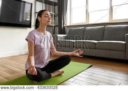 Calm Millennial Caucasian Female In Wireless Headphones Sit In Lotus Pose With Mudra Hands Meditate