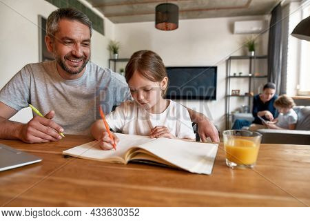 Happy Caucasian Father And Small Daughter Do Homework Write Make Notes In Exercise Book At Home. Smi
