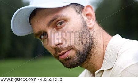 Portrait of a young man in a cap playing golf on the field
