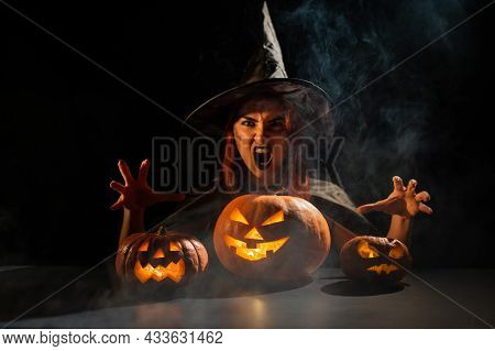 The Evil Witch Casts A Spell On Pumpkins. Portrait Of A Woman In A Carnival Halloween Costume In The