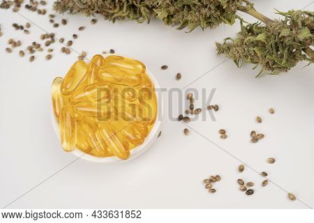 Medicinal Cannabis Buds And Cbd Oil. Marijuana Oil In Medical Capsules Isolated On White Background.