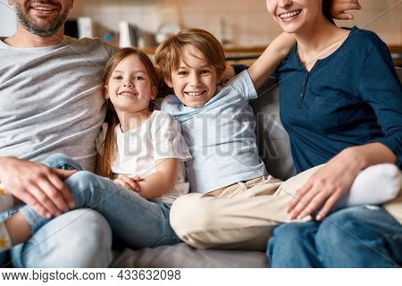 Portrait Of Smiling Little Teen Kids Sit On Sofa Relax At Home With Young Caucasian Parents. Happy S
