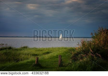 White Sailboat Sailing On A Bay Near A Reed Shore Under A Dark Blue Sky On A Cloudy Autumn Day, Leis