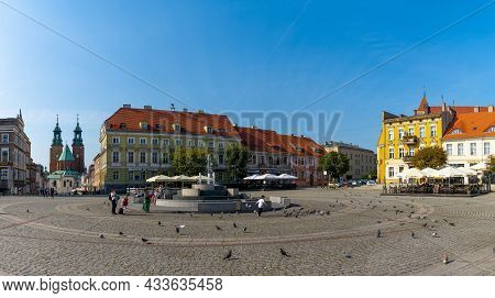 Main City Square In Gniezno With Historic Buildings And The Famous Cathedral In The Background