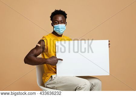 Vaccination Info. Happy Young Black Guy In Mask Pointing At Blank Placard