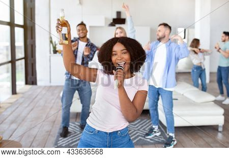 Cheery Black Lady With Bottle Of Beer And Microphone Singing Karaoke On Party With Her Multinational