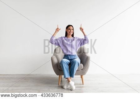 Smiling Woman Sitting In Armchair, Pointing Upwards With Both Hands, Offering Empty Space Above Her