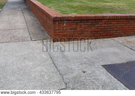 Low Red Brick Retaining Wall Separating A Grassy Area From Sidewalks, Corner View At An Intersection