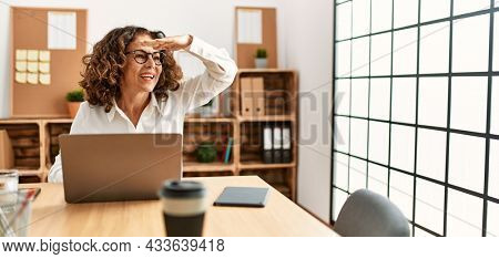 Middle age hispanic woman working at the office wearing glasses very happy and smiling looking far away with hand over head. searching concept.
